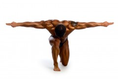 Bodybuilder with arms outstretched side by side of head