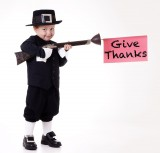 "Child dressed as a pilgrim with a sign that says ""give thanks"""