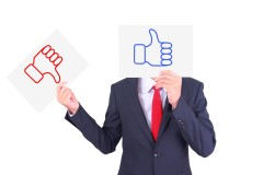 Businessman swap paper to show the contrast of thumbs up and thumbs down