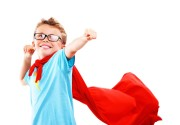 Little boy in glasses dressed up as a superhero